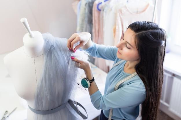 Vue de face du propriétaire de la couturière de mariage qui mesure avec succès des matériaux sur un mannequin de bureau ou d'atelier.