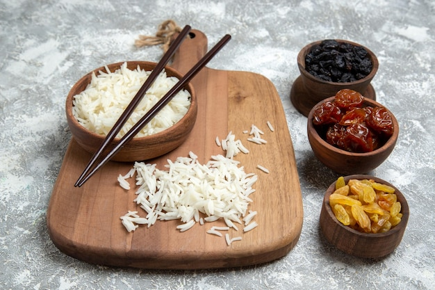 Vue de face du riz cuit savoureux à l'intérieur d'une assiette brune avec des raisins secs sur un espace blanc