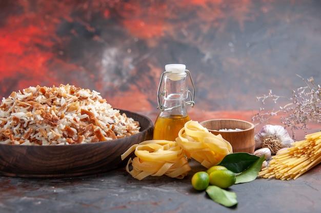 Vue de face du riz cuit avec des tranches de pâte sur un plat de surface sombre