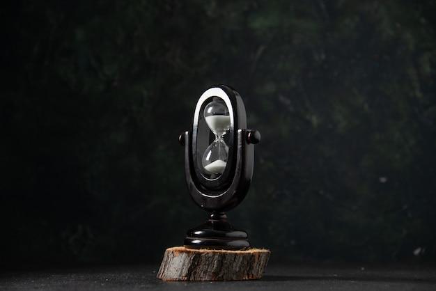 Vue de face du sablier noir sur la surface sombre