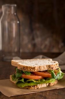 Vue de face du sandwich avec des légumes verts et des tomates