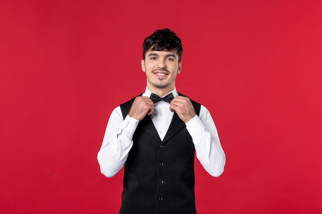 Vue de face du serveur masculin souriant en uniforme avec nœud papillon sur le cou sur le mur rouge