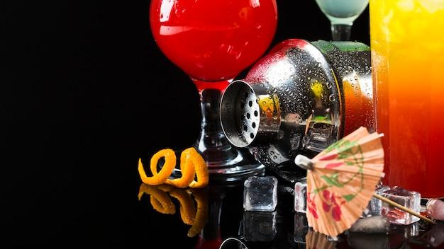 Vue de face du shaker avec cocktails et parapluie