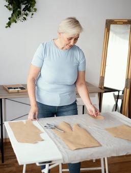 Vue de face du tailleur féminin dans le studio avec tissu