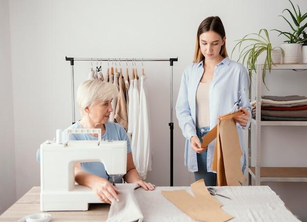 Vue de face du tailleur féminin préparant le tissu pour les vêtements