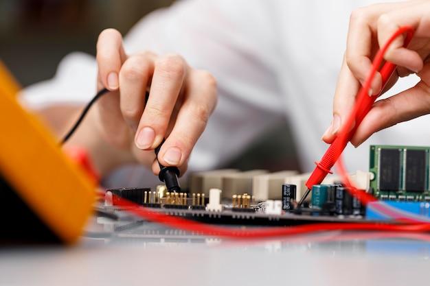 Vue de face du technicien féminin avec carte mère d'ordinateur