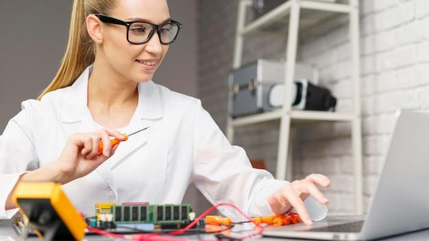 Vue de face du technicien féminin avec électronique et ordinateur portable