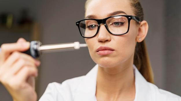 Vue de face du technicien féminin avec fer à souder