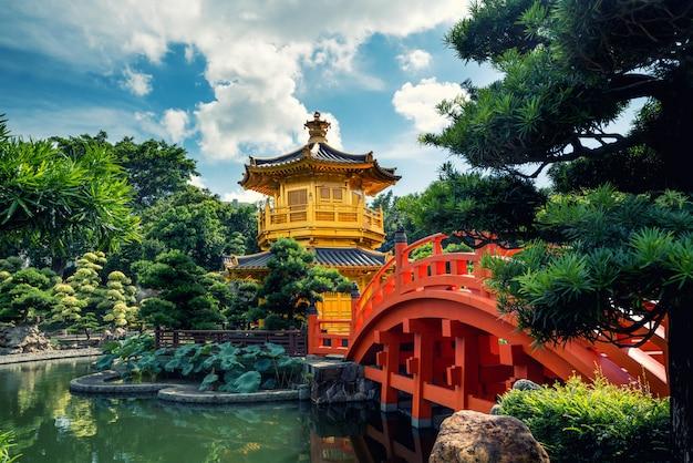 Vue de face du temple du pavillon d'or avec un pont rouge dans le jardin de nan lian
