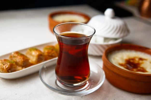 Vue de face du thé dans un verre armudu avec baklava et sucre sur la table