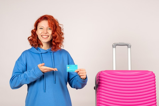 Vue de face du touriste féminin avec sac rose sur mur blanc