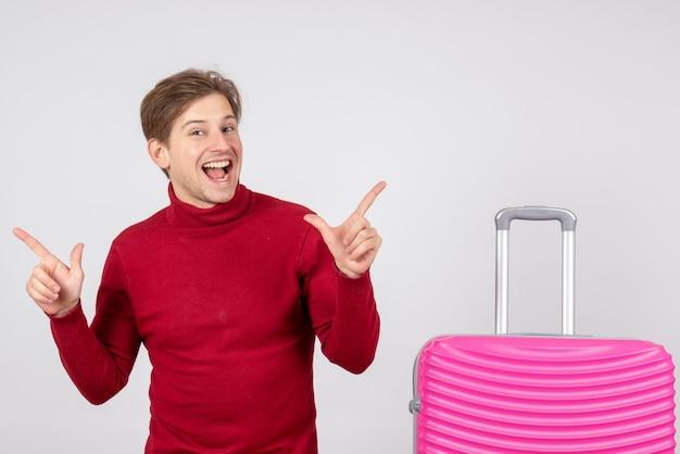 Vue de face du touriste masculin avec sac rose sur mur blanc