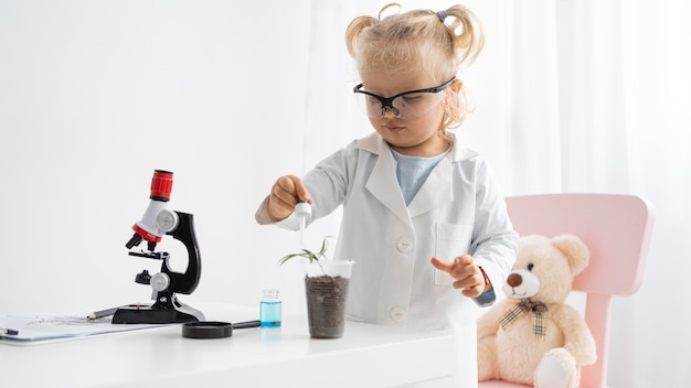 Vue de face du tout-petit mignon apprendre la science avec des plantes et un microscope