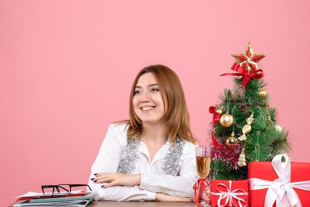 Vue de face du travailleur féminin assis autour de cadeaux de noël sur rose