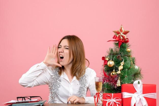 Vue de face du travailleur féminin assis derrière sa table appelant rose