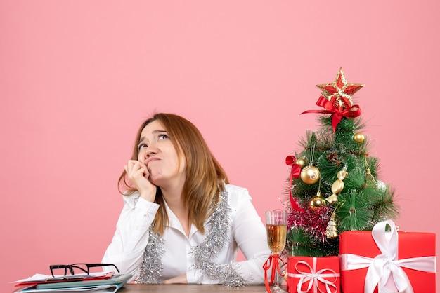 Vue de face du travailleur féminin assis derrière sa table a souligné rêver sur rose