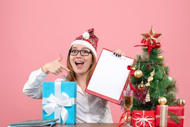Vue de face du travailleur féminin assis et tenant une note de fichier sur rose