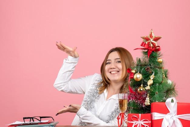 Vue de face du travailleur féminin autour de cadeaux de noël sur rose