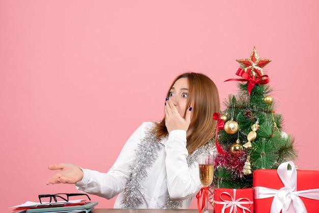 Vue de face du travailleur féminin autour de cadeaux de noël avec visage choqué sur rose