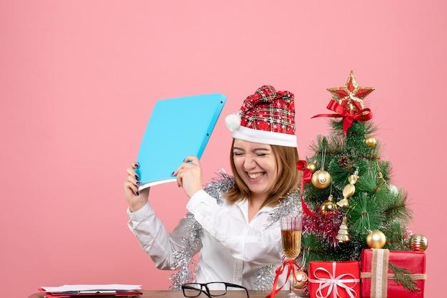 Vue de face du travailleur féminin détenant des documents et se réjouissant de rose