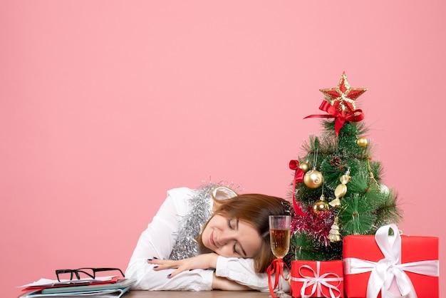 Vue de face du travailleur féminin dormant derrière sa table sur rose