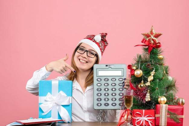 Vue de face du travailleur féminin tenant la calculatrice autour de cadeaux sur rose