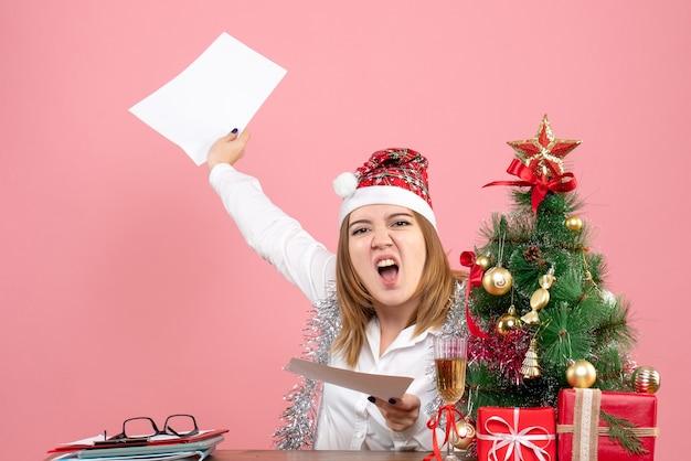 Vue de face du travailleur féminin tenant des documents sur rose