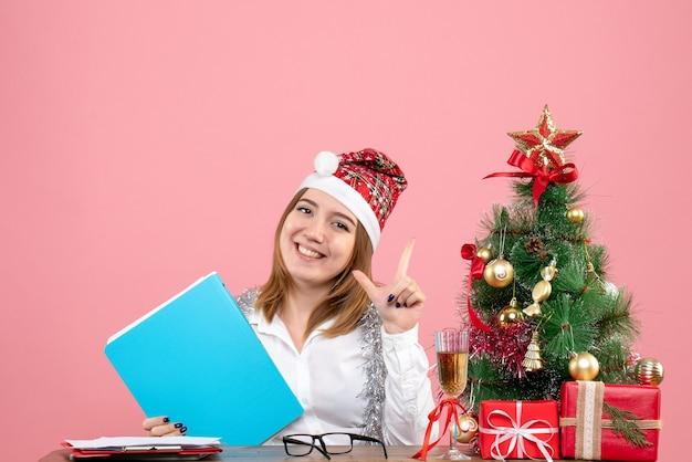 Vue de face du travailleur féminin tenant des documents et souriant sur rose
