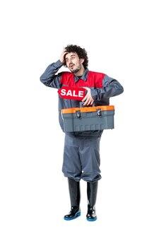 Vue de face du travailleur masculin dans une valise à outils uniforme et vente sur mur blanc