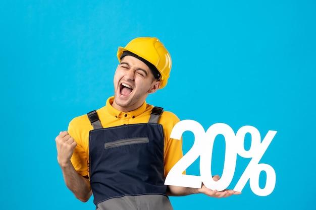 Vue de face du travailleur masculin émotionnel en uniforme sur la surface bleue