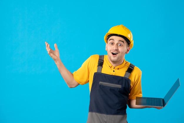 Vue de face du travailleur masculin surpris en uniforme avec ordinateur portable sur bleu