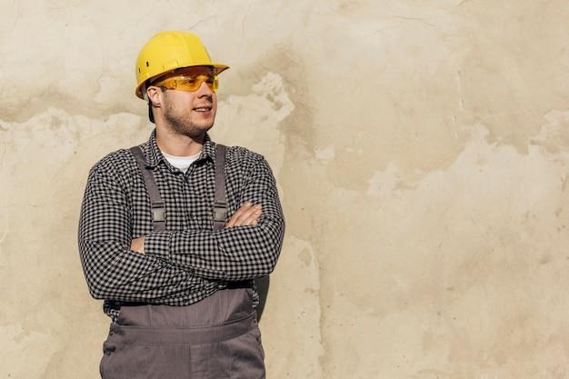 Vue de face du travailleur masculin en uniforme avec casque et lunettes de protection