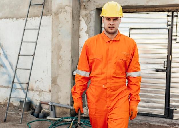 Vue de face du travailleur masculin en uniforme avec casque