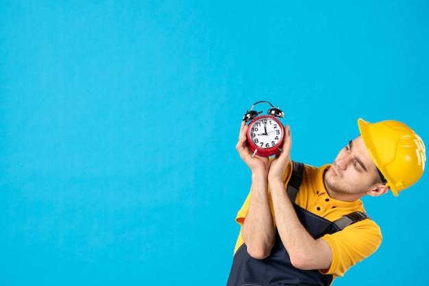 Vue de face du travailleur masculin en uniforme jaune avec des horloges sur bleu