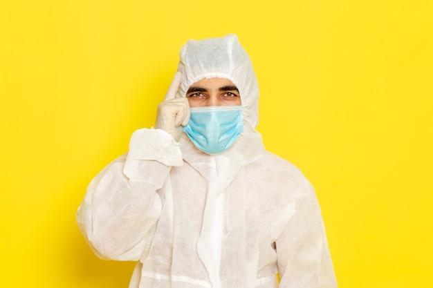 Vue de face du travailleur scientifique masculin en combinaison blanche de protection spéciale avec masque sur le mur jaune clair