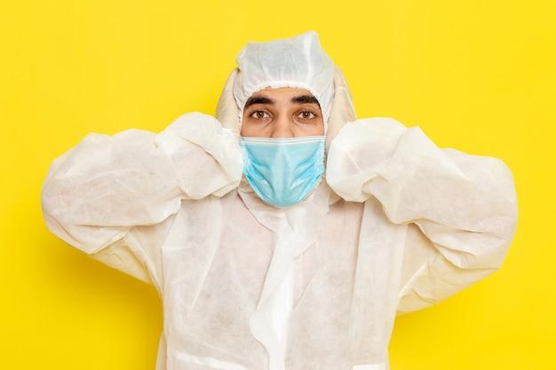 Vue de face du travailleur scientifique masculin en combinaison blanche de protection spéciale et avec masque nerveux sur mur jaune clair