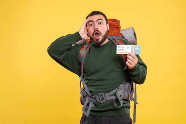 Vue de face du type de voyageur confus avec sac à dos debout sur fond jaune