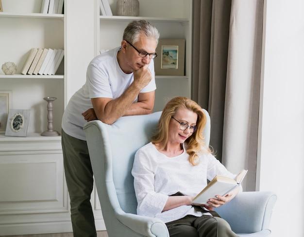 Vue de face du vieil homme et femme lisant un livre