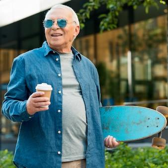 Vue de face du vieil homme avec planche à roulettes