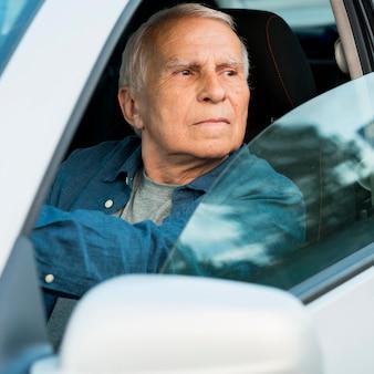 Vue de face du vieil homme en voiture personnelle