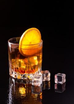 Vue de face du whisky avec orange et glace