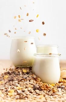 Vue de face du yaourt nature en pots avec du muesli