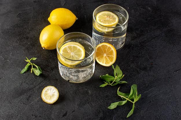 Une vue de face de l'eau avec du citron boisson fraîche fraîche avec des citrons tranchés avec des citrons entiers et des feuilles à l'intérieur de verres transparents sur l'obscurité