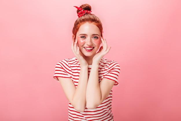 Vue de face de l'élégante jeune femme avec des patchs oculaires regardant la caméra. photo de studio de fille au gingembre faisant des soins de la peau isolé sur fond rose.