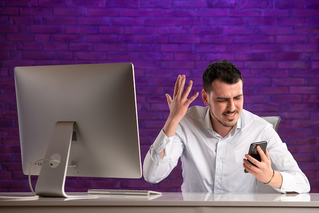 Vue de face employé de bureau masculin assis derrière son lieu de travail et parler