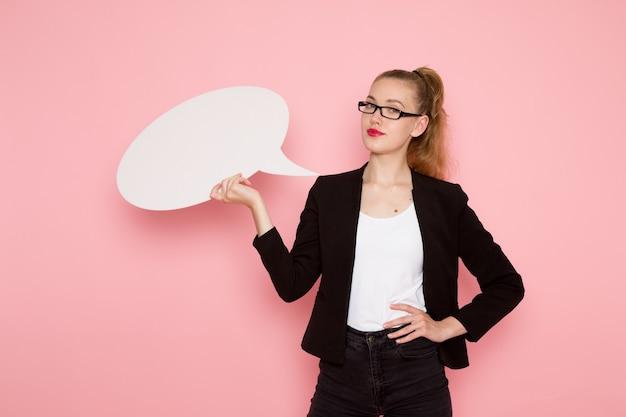 Vue de face de l'employé de bureau en veste noire stricte souriant tenant une carte blanche sur un mur rose