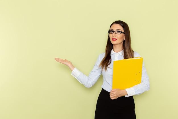 Vue de face de l'employée de bureau en chemise blanche et jupe noire tenant un fichier jaune sur le mur vert