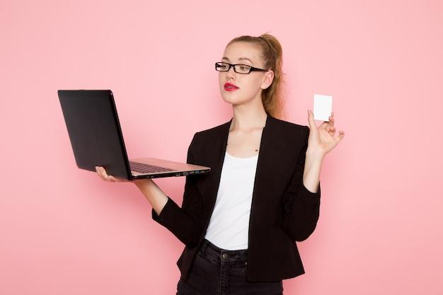 Vue de face de l'employée de bureau en veste noire stricte à l'aide de son ordinateur portable tenant la carte sur le mur rose
