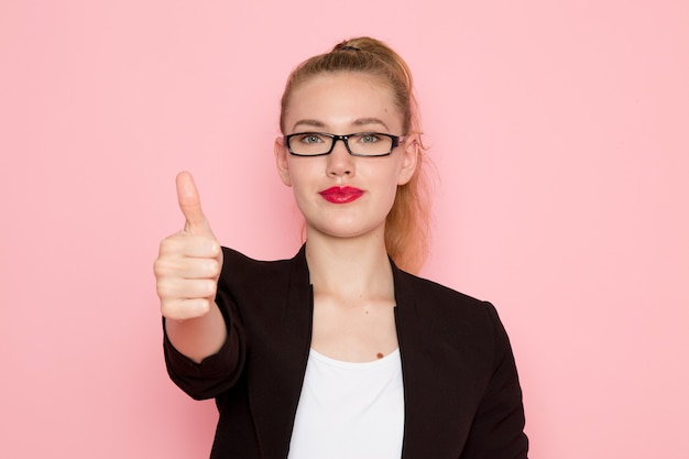 Vue de face de l'employée de bureau en veste noire stricte montrant comme signe sur mur rose clair