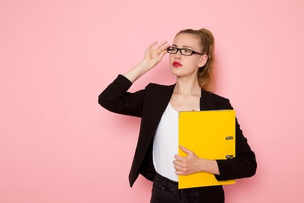 Vue de face de l'employée de bureau en veste noire stricte tenant des fichiers jaunes sur un mur rose clair